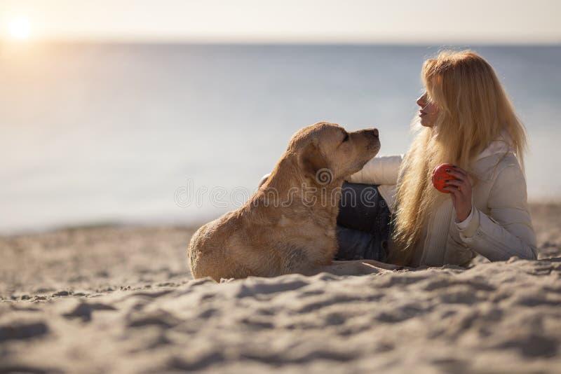 Stäng sig upp ståenden av den härliga långa haired flickan med hennes labradorhund på stranden royaltyfria foton