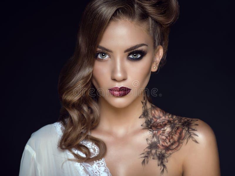 Stäng sig upp ståenden av den härliga modellen med konstnärligt smink och frisyren Blom- kroppkonst på hennes skuldra Idealt kvin arkivfoto