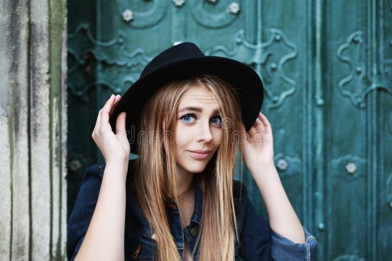 Stäng sig upp ståenden av den härliga skämtsamma le flickan som bär den stilfulla bredbrättade svarta hatten Modell Looking på ka royaltyfri bild