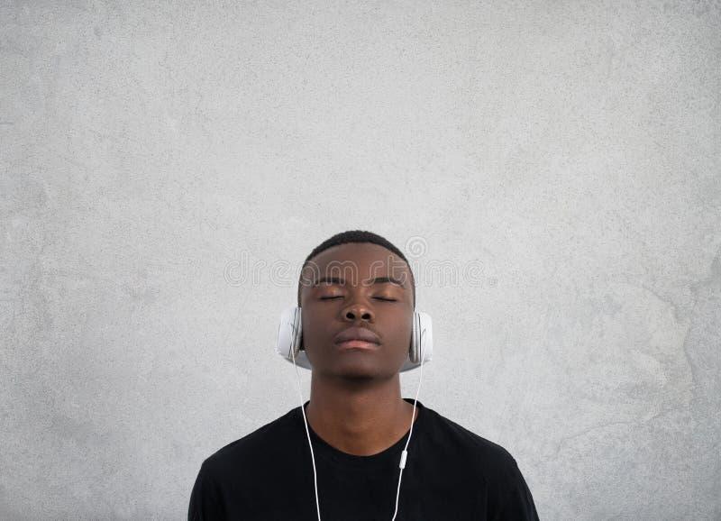 Stäng sig upp ståenden av den mörker flådde mannen med stängda ögon, har hörlurar, lyssnar till favorit- musik tycker om tonåring fotografering för bildbyråer