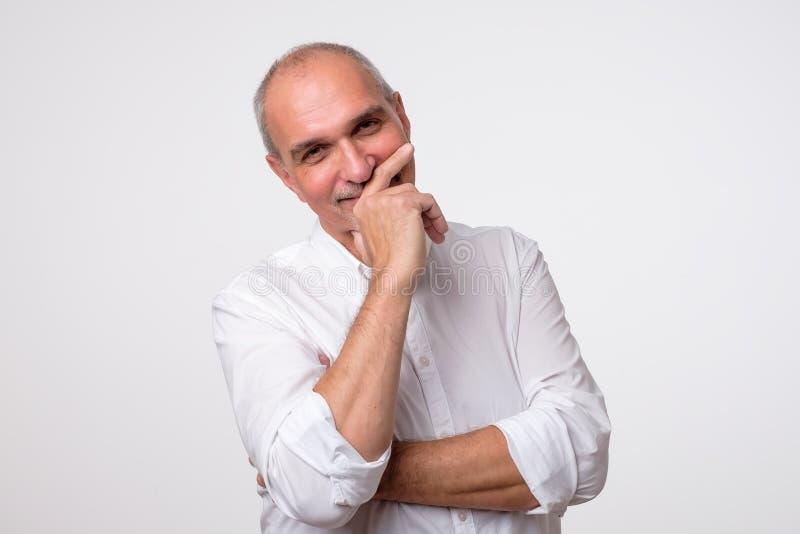 Stäng sig upp ståenden av den mogna latinamerikanska mannen som skrattar och täcker hans mun med handen över vit bakgrund arkivbilder