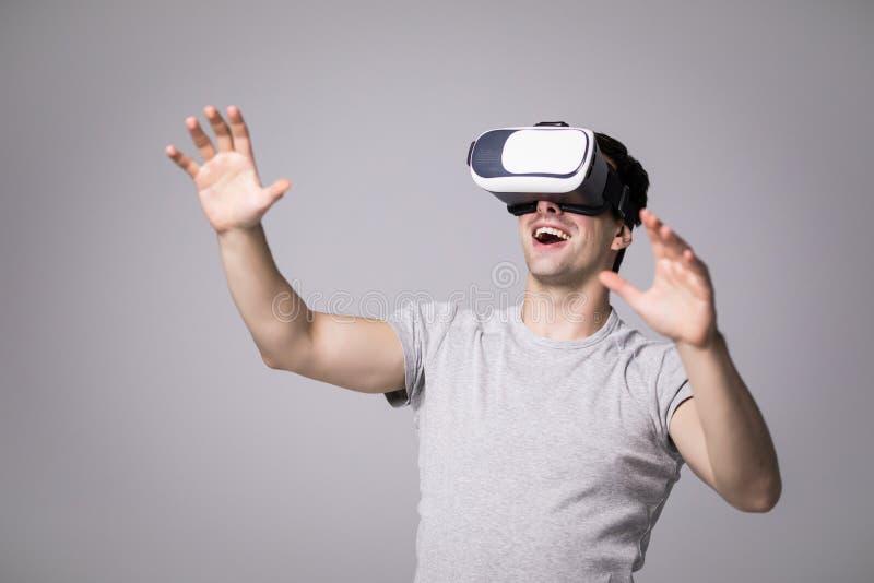 Stäng sig upp ståenden av den stiliga mannen i grå t-skjorta som erfar virtuell verklighet genom att använda VR-hörlurar med mikr royaltyfria foton