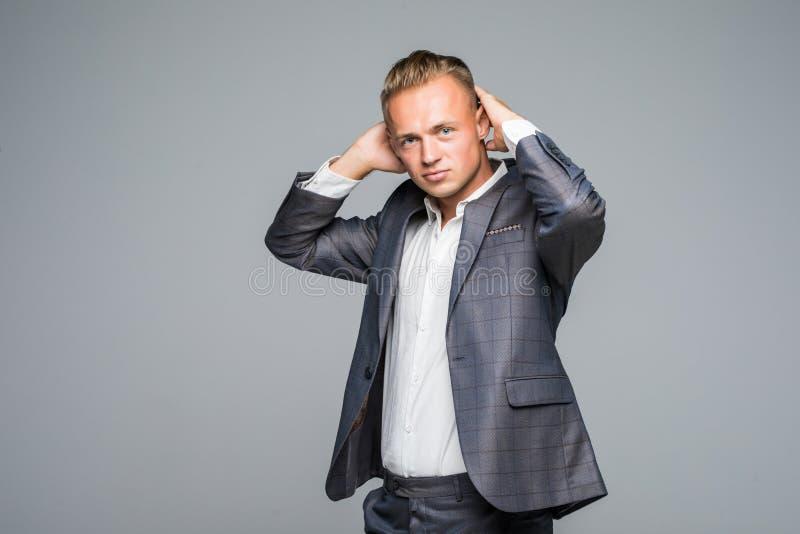 Stäng sig upp ståenden av den stiliga säkra manliga mannen i omslaget som trycker på hans hår på grå färger arkivbilder