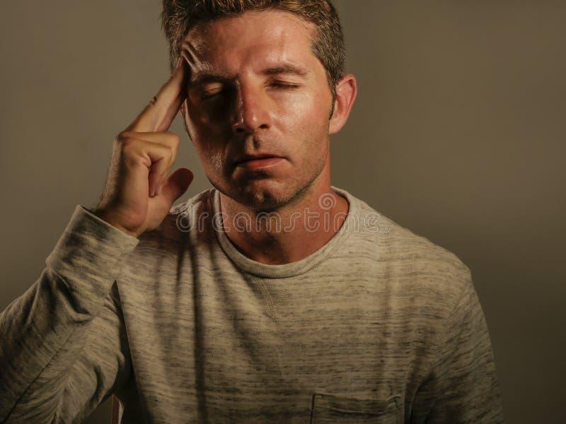 Stäng sig upp ståenden av den unga attraktiva mannen med fingrar på head tempo i deprimerad känsla för spänningslidandehuvudvärke arkivbilder
