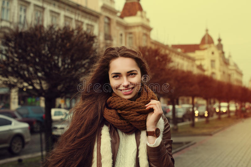 Stäng sig upp ståenden av den unga härliga trendiga le flickan som bär stilfull kläder som står på gatan gammal stad royaltyfri fotografi