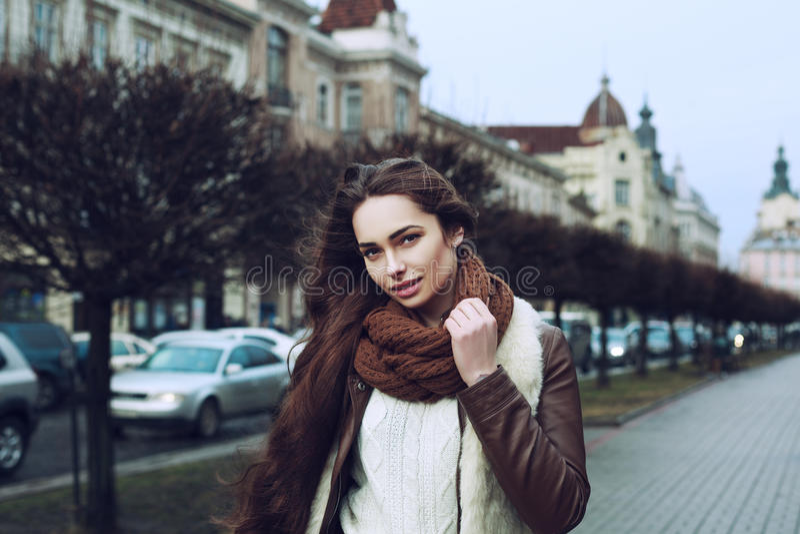 Stäng sig upp ståenden av den unga härliga trendiga le kvinnan som bär stilfull kläder som står på gatan gammal stad royaltyfria foton