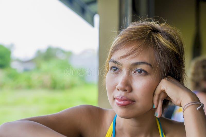 Stäng sig upp ståenden av den unga lyckliga härliga asiatiska kvinnan från Indonesien som ser fundersamt och eftertänksamt dagdrö royaltyfri bild
