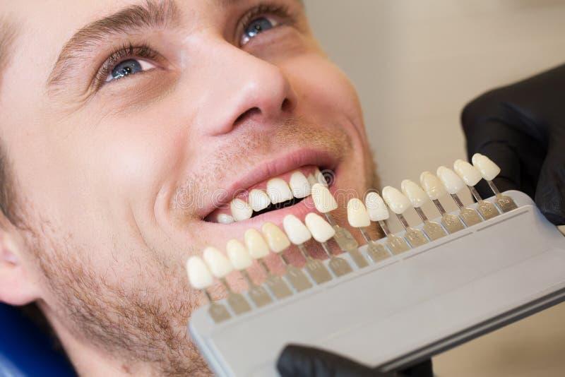 Stäng sig upp ståenden av den unga mannen i tandläkarestol, kontrollera och välj färgen av tänderna Tandläkaren gör processen av  arkivbild