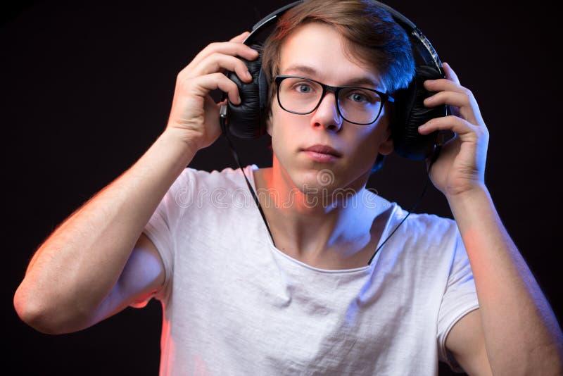 Stäng sig upp ståenden av den unga mannen som kontrollerar ljudet i hörlurar royaltyfri fotografi