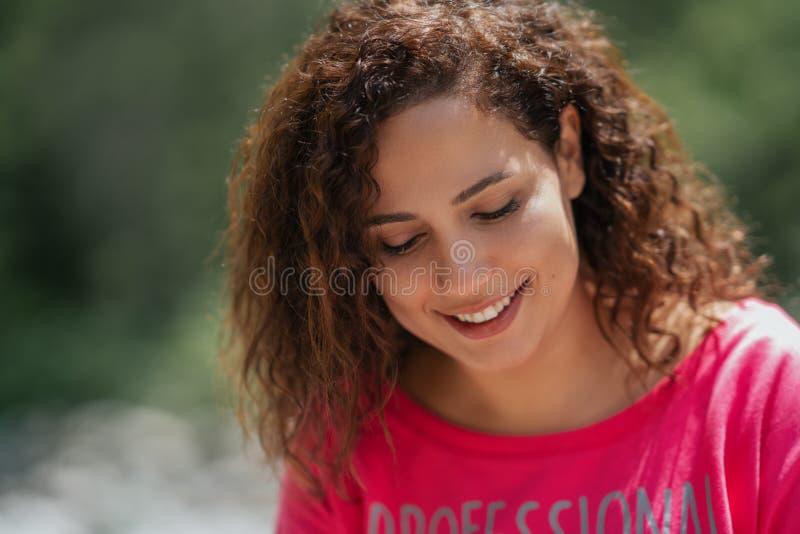 Stäng sig upp ståenden av en gladlynt lockig ung kvinna som utomhus ler arkivbilder