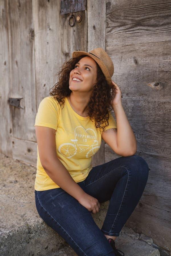 Stäng sig upp ståenden av en gladlynt lockig ung kvinna som utomhus ler fotografering för bildbyråer