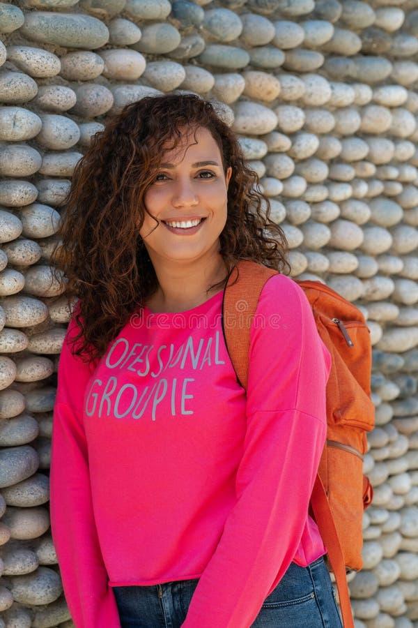 Stäng sig upp ståenden av en gladlynt lockig ung universitetsstudentkvinna som utomhus ler arkivbild