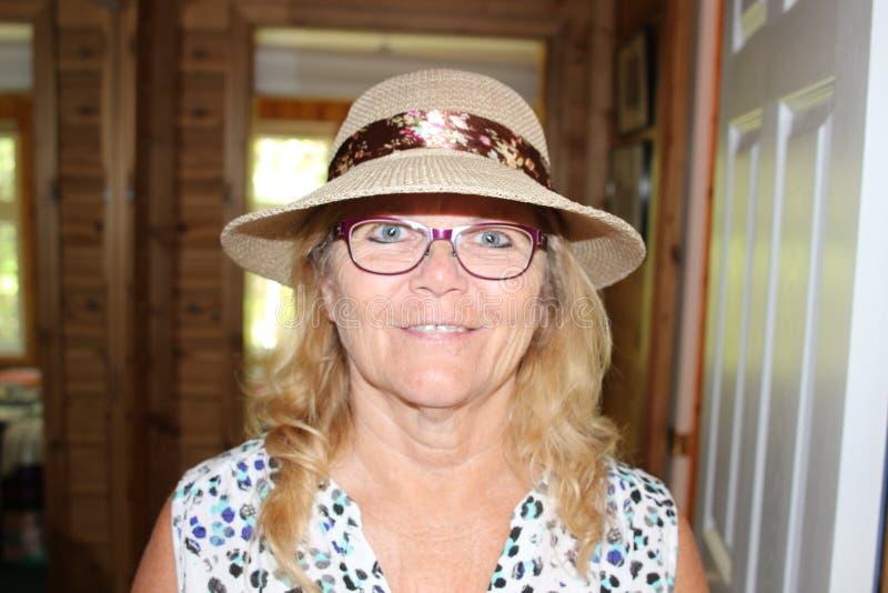 Stäng sig upp ståenden av en härlig äldre hög kvinna som ler med hatten arkivbilder