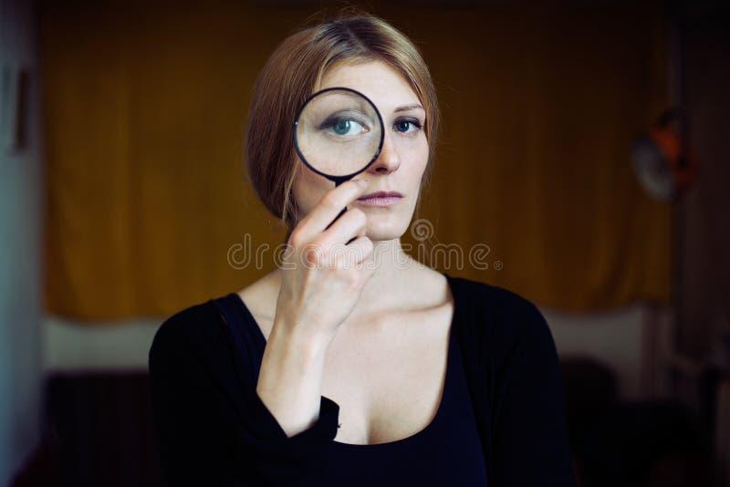 Stäng sig upp ståenden av en härlig kvinna med en glass förstoringsapparat royaltyfria foton