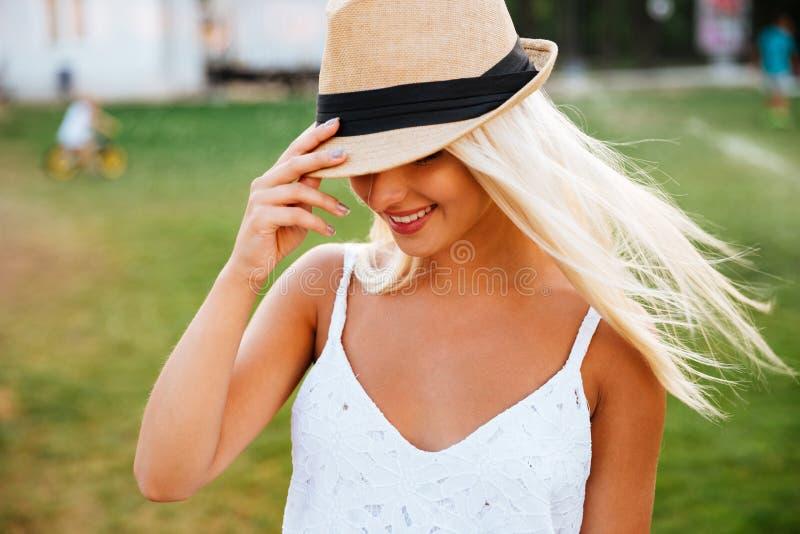 Stäng sig upp ståenden av en le ung kvinna i hatt royaltyfria foton