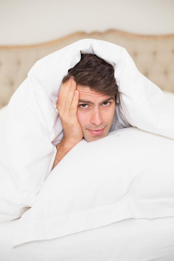 Stäng sig upp ståenden av en man som vilar i säng fotografering för bildbyråer