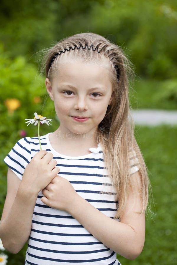 Stäng sig upp ståenden av en sju år liten flicka, mot backgroun arkivfoton