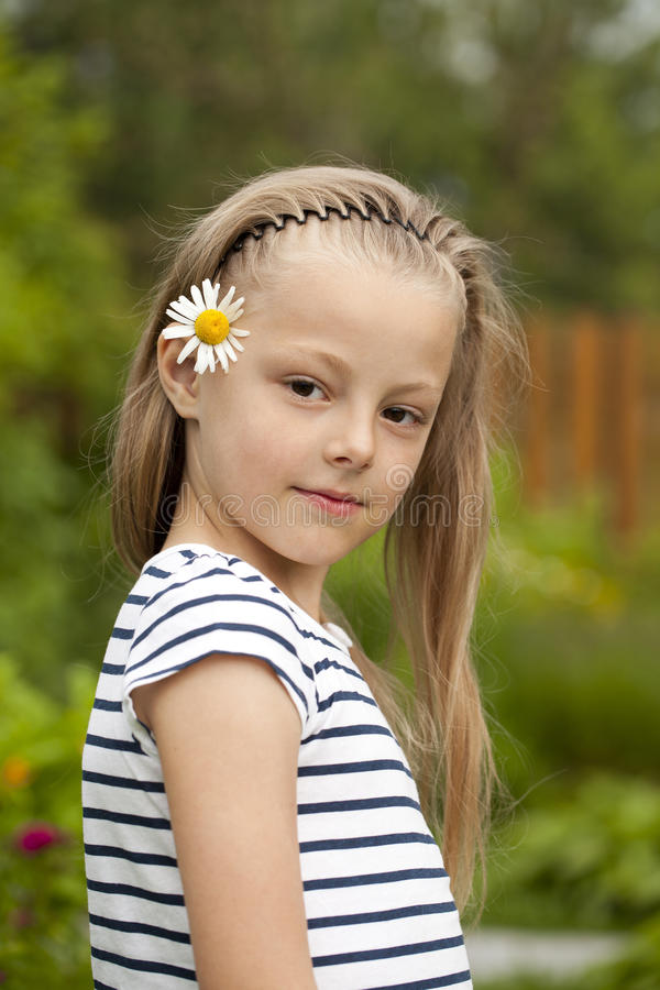 Stäng sig upp ståenden av en sju år liten flicka, mot backgroun arkivfoto