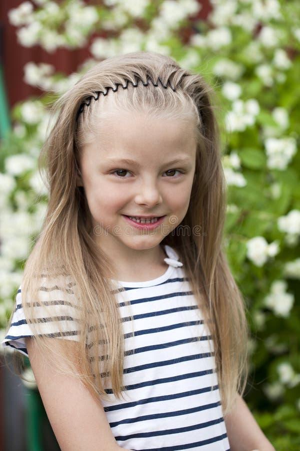 Stäng sig upp ståenden av en sju år liten flicka, mot backgroun royaltyfria foton