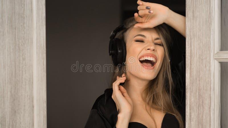 Stäng sig upp ståenden av en sjungande kvinna i hörlurar Hon sjunger tidigt på morgonen hemma royaltyfria foton
