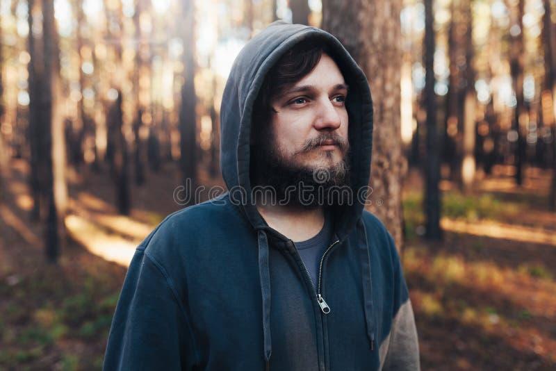Stäng sig upp ståenden av en skäggig hipsterturist i grå huvman i solljusträskogen arkivfoto