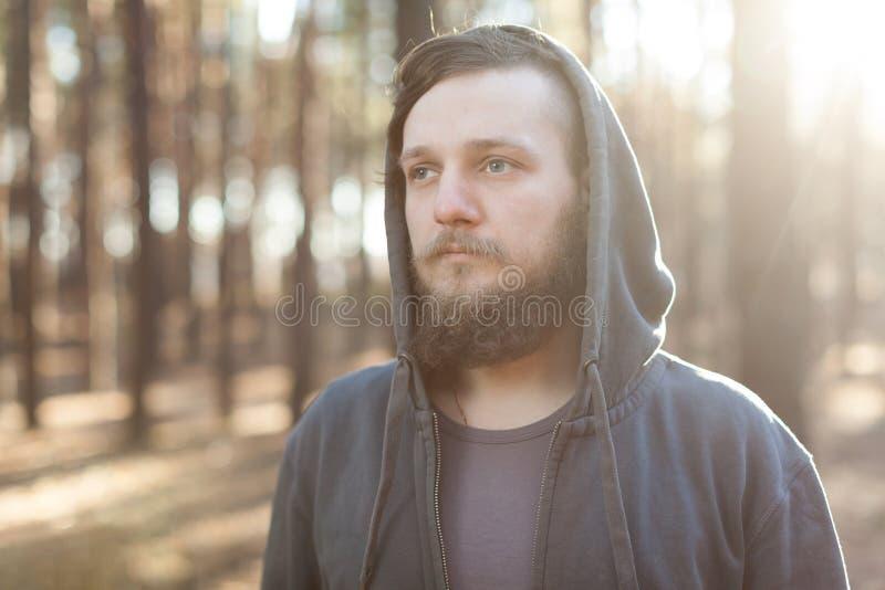 Stäng sig upp ståenden av en skäggig hipsterturist i grå huvman i solljusträskogen fotografering för bildbyråer