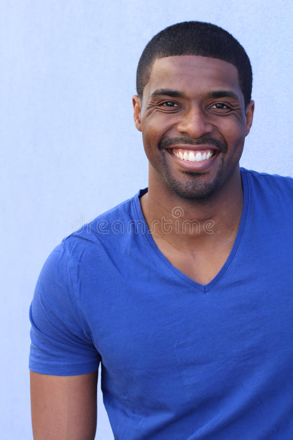 Stäng sig upp ståenden av en skratta afrikansk amerikanman som poserar mot blå bakgrund arkivbilder