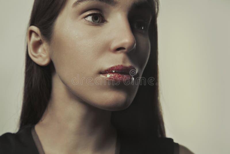 Stäng sig upp ståenden av en ung kvinna med ren ny hud, mörka färger royaltyfria bilder