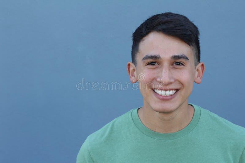 Stäng sig upp ståenden av en ung latinamerikansk tonåringman som ser kameran med ett glat le uttryck, mot en blå bakgrund royaltyfri fotografi