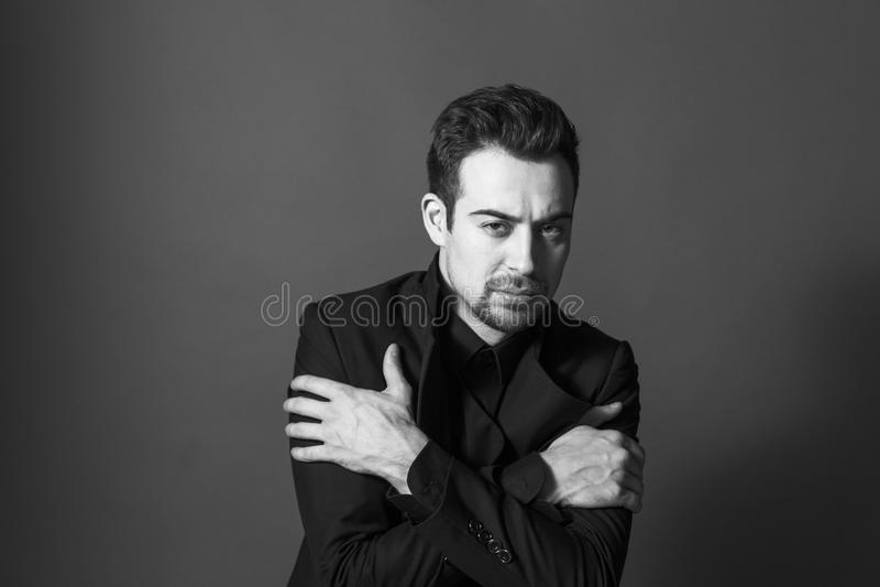 Stäng sig upp ståenden av en ung stilig man i en dräkt, armcrosse arkivbilder