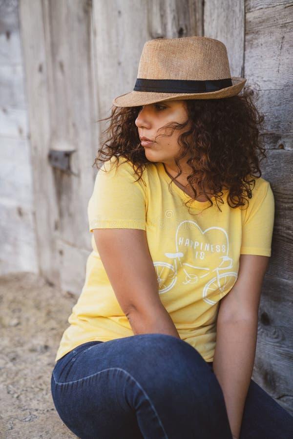 Stäng sig upp ståenden av ett lockigt sammanträde för ung kvinna utomhus fotografering för bildbyråer