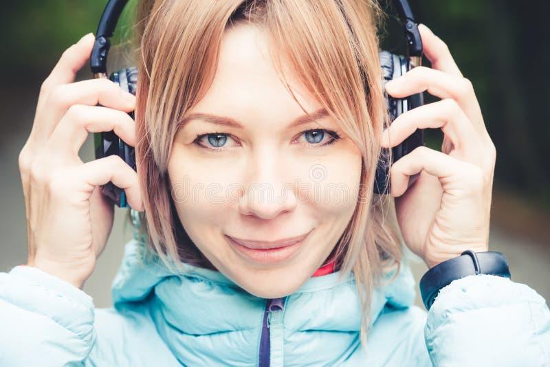 Stäng sig upp ståenden av härlig hållande hörlurar för en ung kvinna som utomhus lyssnar till musik i den glade musiken för skoge royaltyfri fotografi