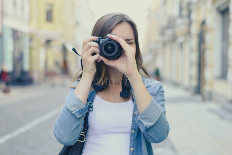 Stäng sig upp ståenden av kvinnan i tillfällig kläder som tar fotoet på hennes digitala kamera Lens är i fokus, den suddiga stads arkivbilder