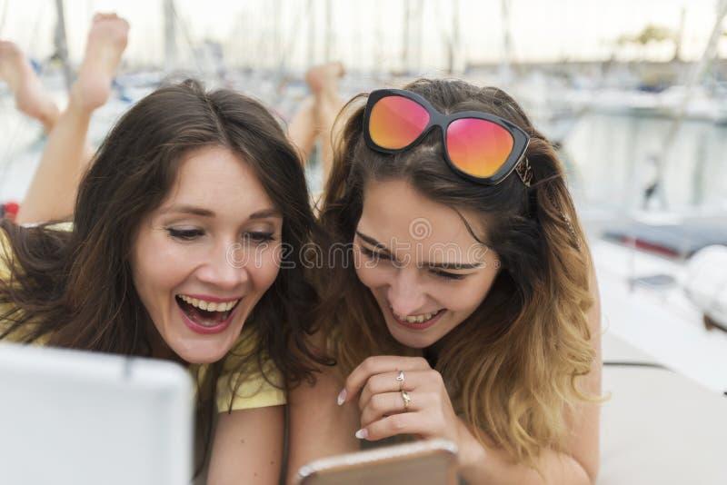 Stäng sig upp ståenden av två upphetsade flickvänner med mobiltelefoner som ner ligger och in camera skrattar och ser royaltyfri foto