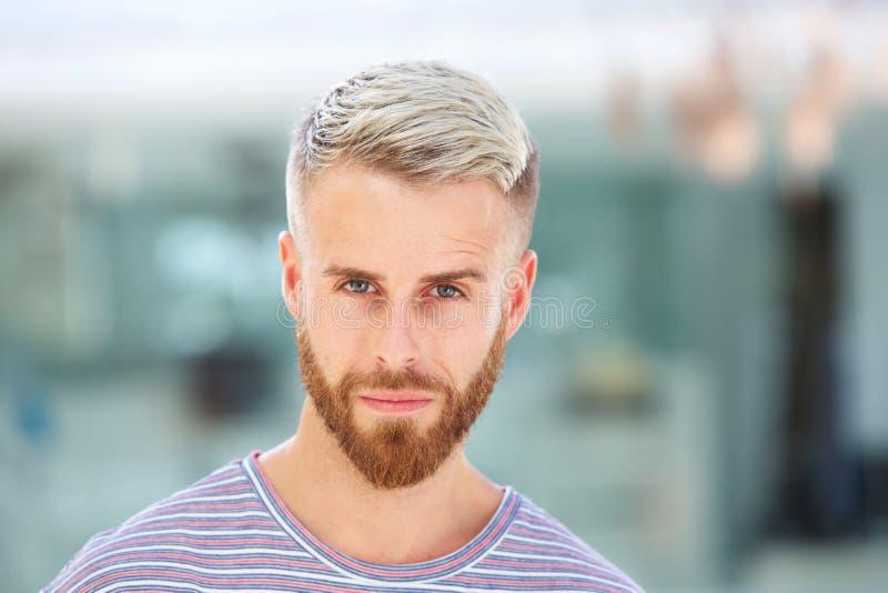 Stäng sig upp stilig ung man med att stirra för skägg royaltyfria foton