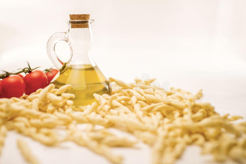 Stäng sig upp stilleben av den italienska handgjorda ferrettoen för pastafusillial med tomatpuré och extra jungfrulig olivolja på royaltyfria foton