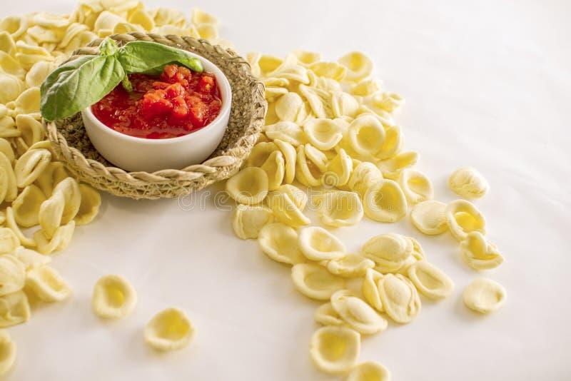 Stäng sig upp stilleben av den italienska handgjorda pastaorecchiettepugliesien med tomatpuré och basilika på vit bakgrund royaltyfri fotografi