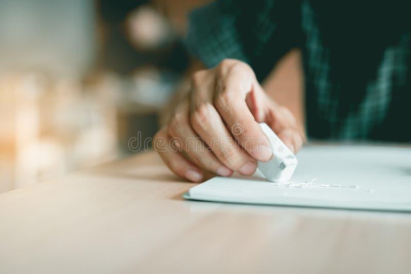 Stäng sig upp studenten som använder radergummit för, redigerar fel arkivfoton