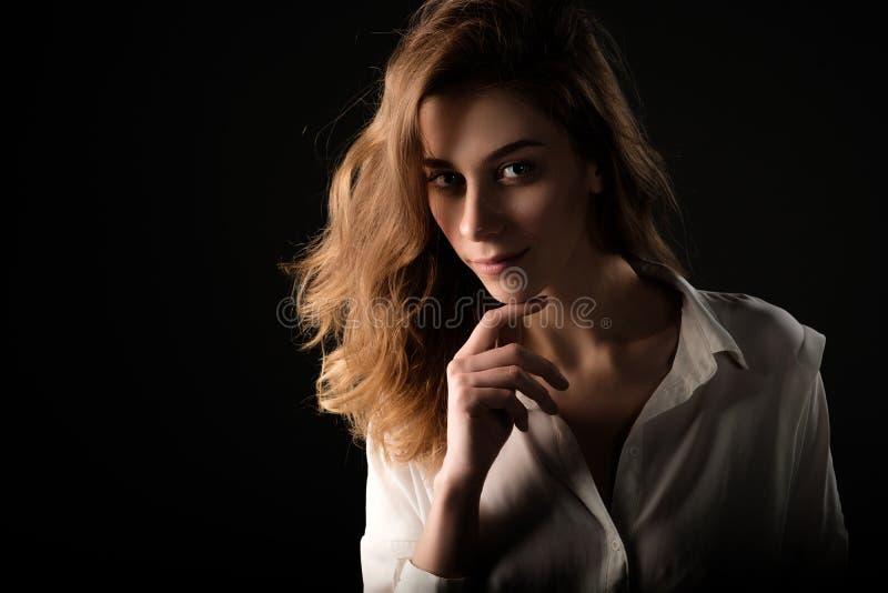 Stäng sig upp studioståenden av den unga le kvinnan i den vita blusen på svart bakgrund arkivbilder
