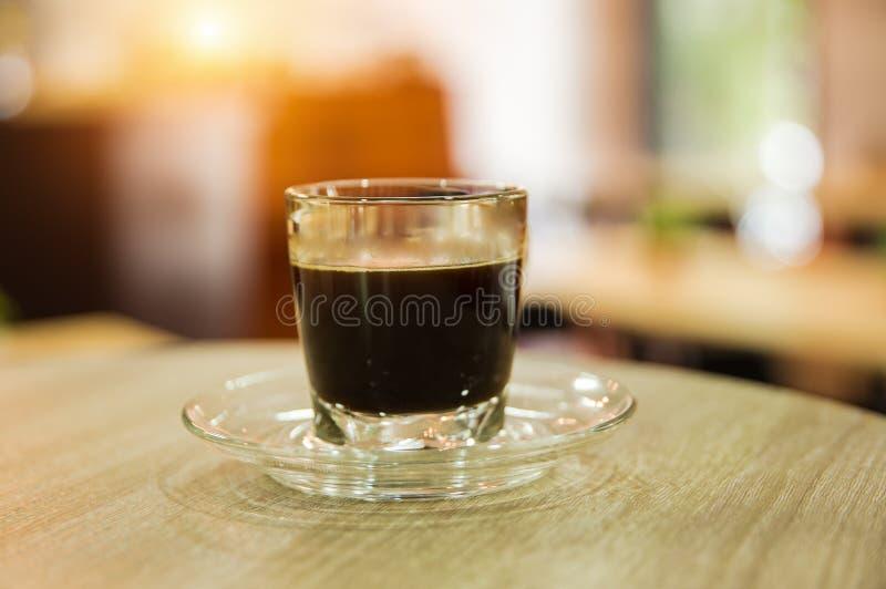 Stäng sig upp svart kaffe, oskarpt ljus omkring arkivbilder