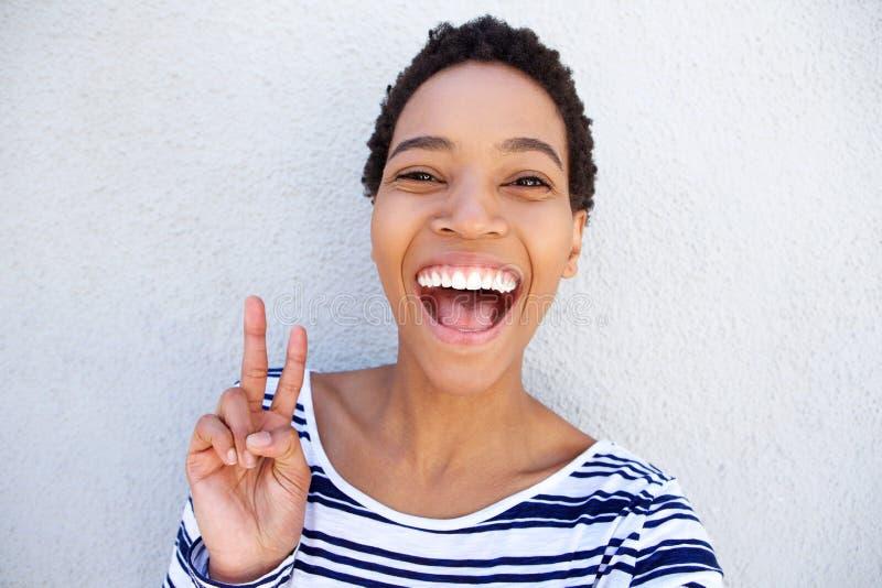 Stäng sig upp svarta kvinnan som skrattar och rymmer fredhandtecknet arkivfoto