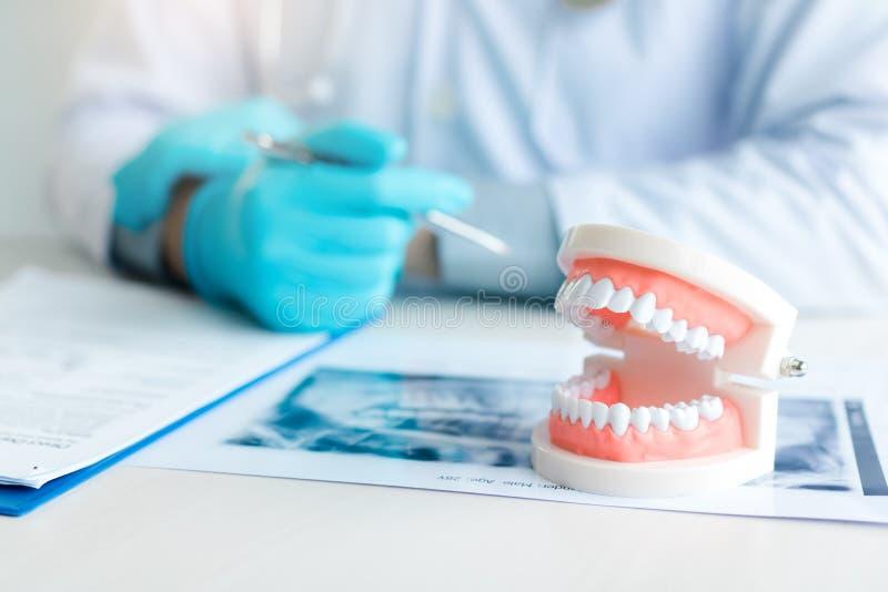 Stäng sig upp tandproteser med tandläkaren som arbetar på tabellen i klinik royaltyfri fotografi