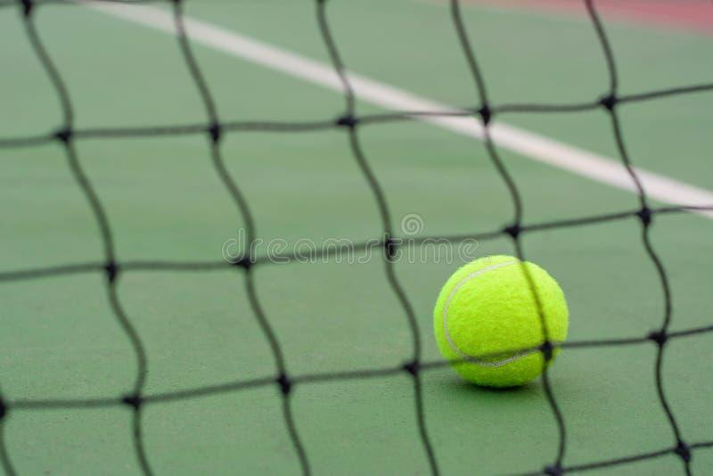 Stäng sig upp tennisboll och gör suddig netto på domstolbakgrund royaltyfri bild