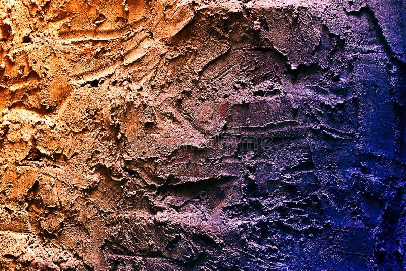Stäng sig upp textur av bicolor orange blå präglad murbruk på väggen arkivfoto