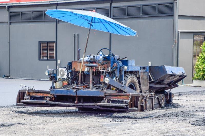 Stäng sig upp tillbaka av det blåa maskineriet för att bära den lilla stenen med blandat med asfalten för att hälla på golvet som arkivfoto