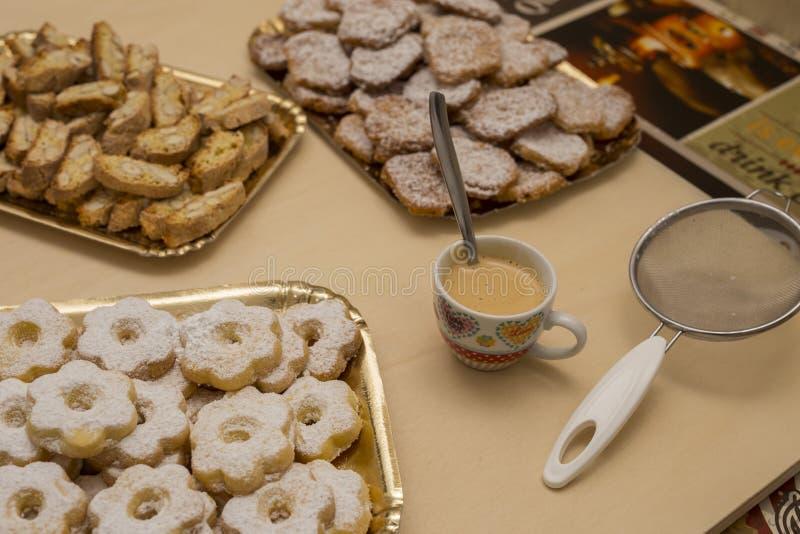 Stäng sig upp typisk genoese kexcanestrelli och cantucci med koppen kaffe royaltyfri bild