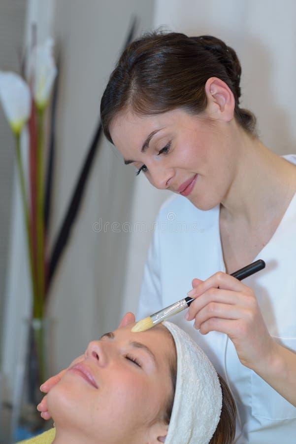 Stäng sig upp ung kvinna och cosmetologist i brunnsort arkivfoto