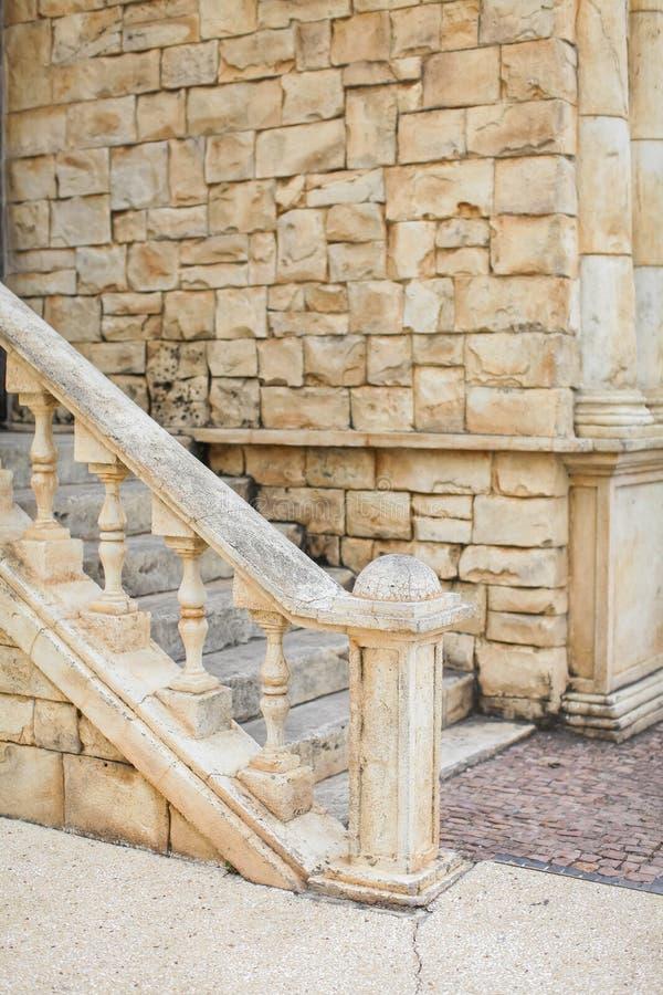 Stäng sig upp utomhus- sikt av den lilla och smala stenstairecasen åldriga sandfärgmoment som fogas ihop till tegelstenväggen par royaltyfri fotografi