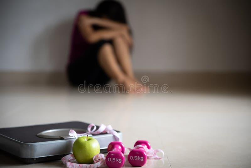 Stäng sig upp vägningsskala framme av den upprivna kvinnan med att mäta bandet, den rosa hanteln och det gröna äpplet Sund livsst arkivbilder