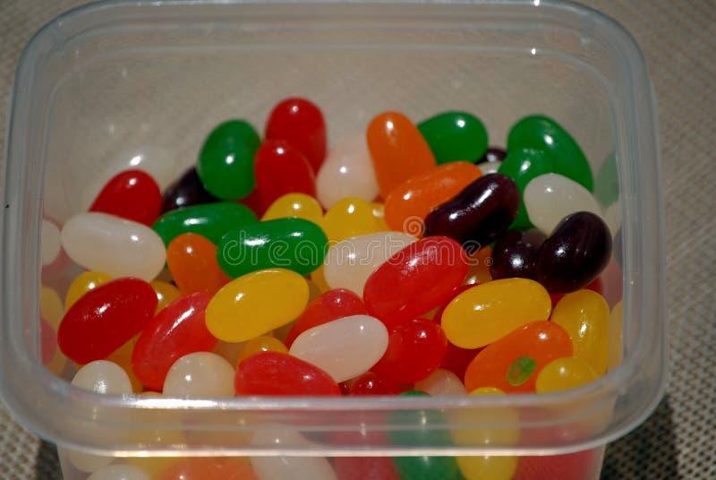 Stäng sig upp vision av smakliga söta jellybeans i en loppbehållare royaltyfria foton